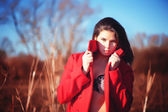 Brunette woman in red coat with underwear outdoor — Stock Photo