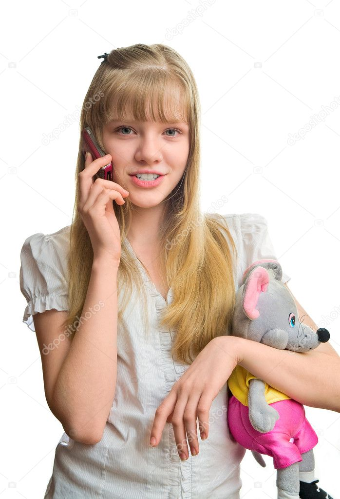 Young blonde girl talking to mobile phone and hold a mouse toy in her hand — Stock Photo #8208275