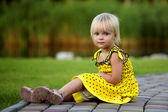 Summer portrait of beautiful baby girl on the lawn — Stock Photo