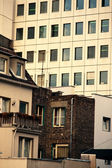 Rows of apartment windows above conventional homes — Stock Photo