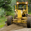 Grader resurfacing narrow rural road - Stock Photo