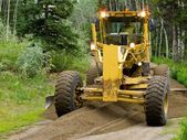 Grader resurfacing narrow rural road — Stock Photo
