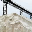 Pile of sea salt under conveyor of saline refinery - Stock Photo