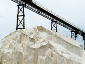 Pile of sea salt under conveyor of saline refinery — Stock Photo