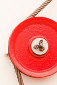 Red fairlead pulley and steel cable — Stock Photo