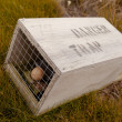 Stock Photo: Small animal trap with written warning for humans