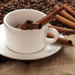 White coffee mug, beans and cinnamon sticks on sacking - Stock Photo