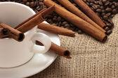 White coffee mug, beans and cinnamon sticks on sacking — Stock Photo