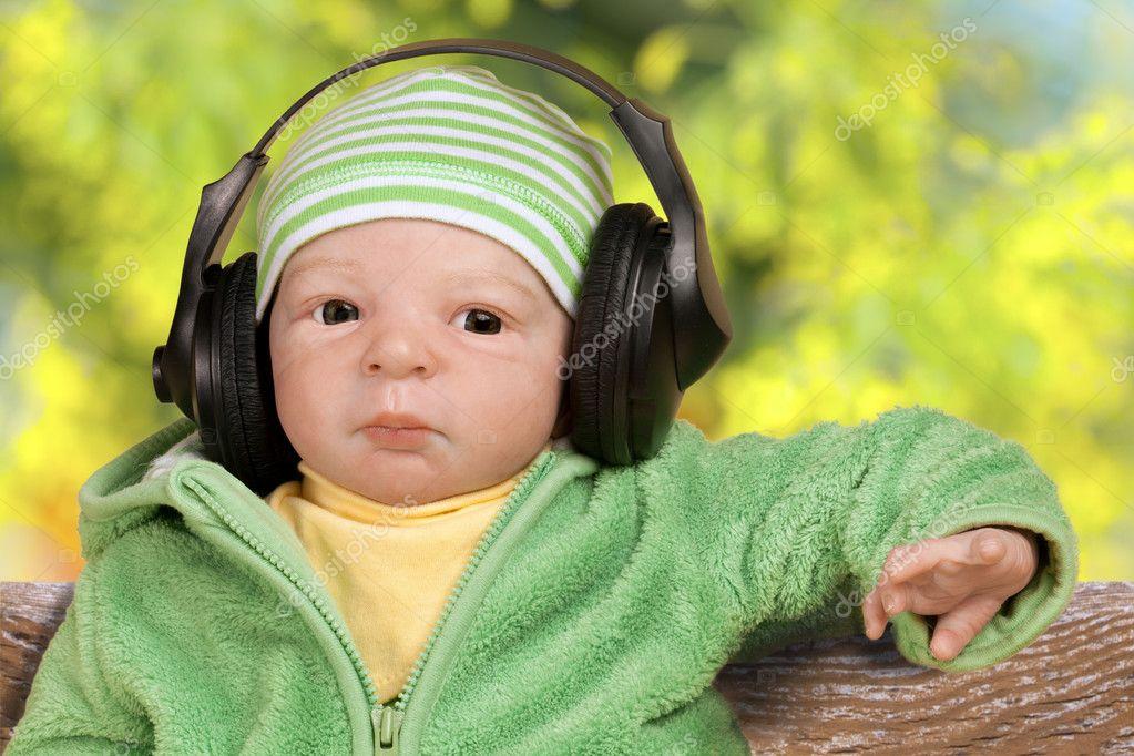 可爱的小宝贝娃娃用耳机听音乐公园 — 照片作者 marischka
