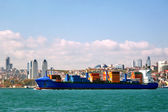 Container ship sails in front of the city — Stock Photo