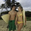 Young couple at the beach with their surf boards — Stok fotoğraf