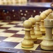 Chess pieces on wooden playboard — Stock Photo #9685533