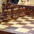 Chess pieces on wooden playboard — Stock Photo #9685539