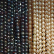 Lot of beads from white and black pearl — Stock Photo