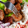 Fork on a dish with rice and meat - Stock Photo