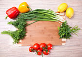 Kitchen chopping board with vegetables, a tomato and a lemon — Stock Photo