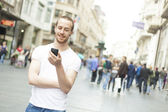 Young Man with cell phone walking in city — Stock Photo