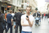 Young Man in City with mobile phone — Stock Photo