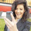 Stock Photo: Young Woman with funny hair smile using cell phone walking