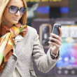Woman with sunglasses and cell phone walking — Stock Photo #10059241
