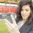 Stock Photo: Young Woman with cell phone walking