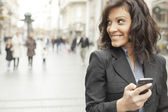 Young Woman with smartphone walking on street — Stock Photo