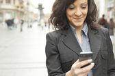 Businesswoman with smartphone walking on street — Zdjęcie stockowe