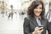 Young Woman with smile and smartphone walking on street — Stock Photo