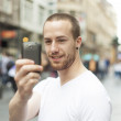 Stock Photo: Men on street photographing with mobile phone