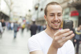 Young Man with cell phone walking — Stock Photo
