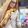 Woman with smartphone walking on street — Stock Photo