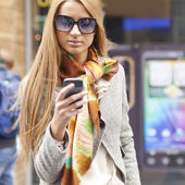 Young Fashionable Woman with smartphone walking on street — Stock Photo
