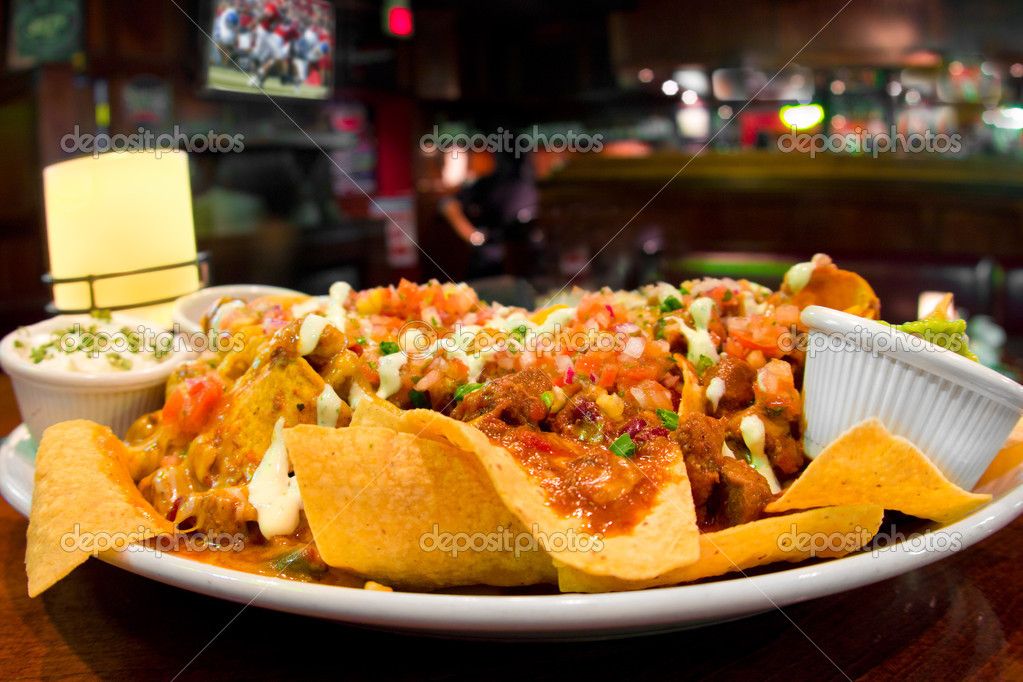 Loaded nachos with chili and cheese in sports bar setting, with beer and football game on tv in the background — Stock Photo #8517814