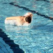 Foto Stock: Young athletic mworking out swimming in pool