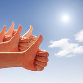 Thumbs up on background of blue sky and white clouds — Stock Photo
