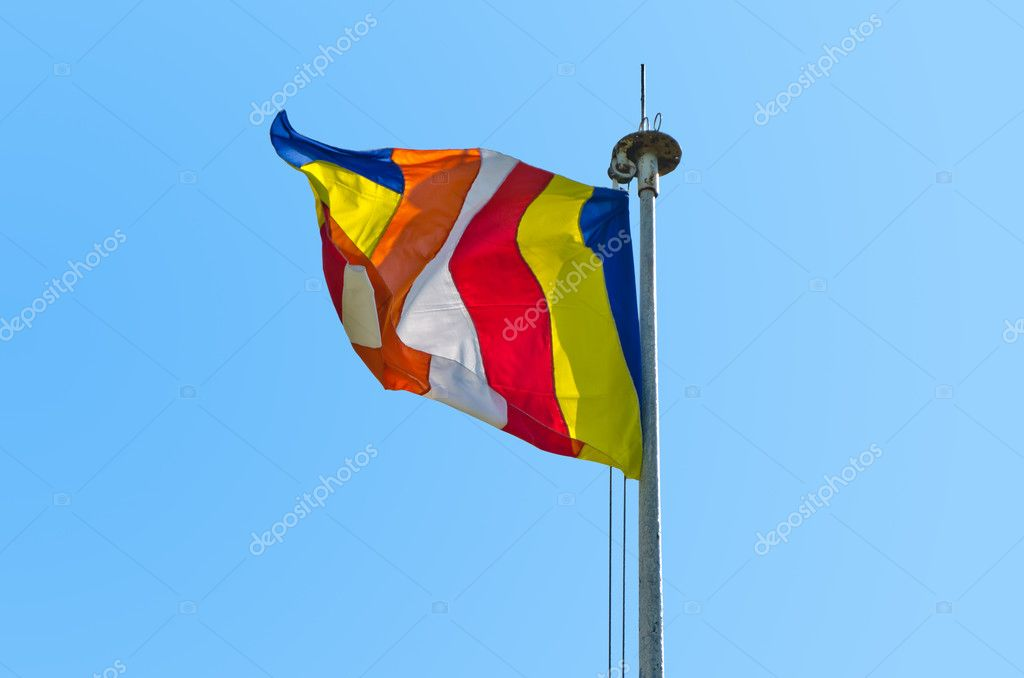 Symbolic flag of Buddhism against the cloudless sky. The six vertical bands of the flag represent the six colors of the aura which Buddhists believe emanated from the body of the Buddha when he attained enlightenment — Stock Photo #10138679