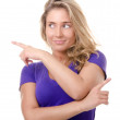 Blonde young woman makes a gesture pointing — Stock Photo #8418783