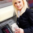 Woman with money at automatic teller — Stock Photo #10141531