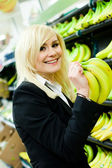 Smiling woman buying bananas — Stock Photo