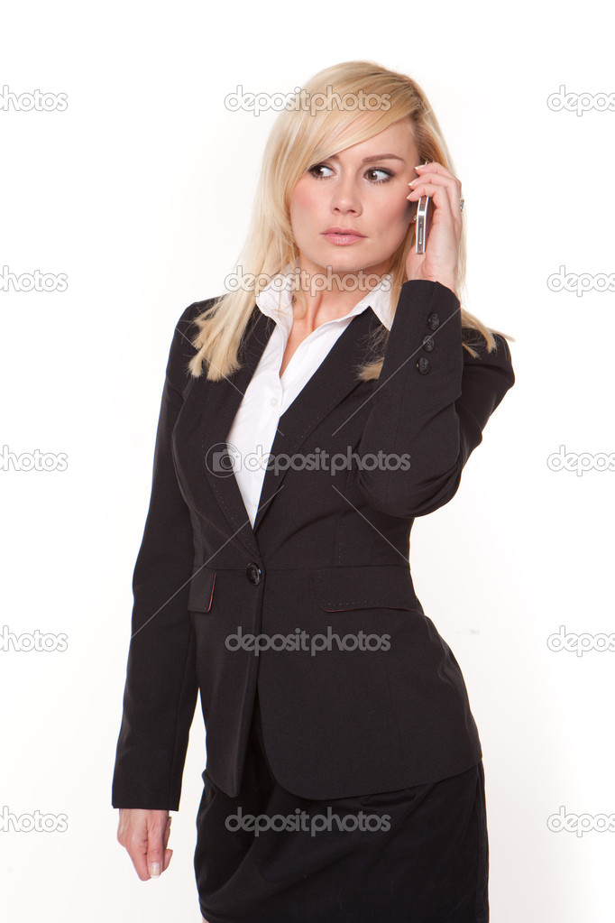 Blonde stylish businesswoman standing chatting on her mobile phone and looking off camera  Stock Photo #10342809