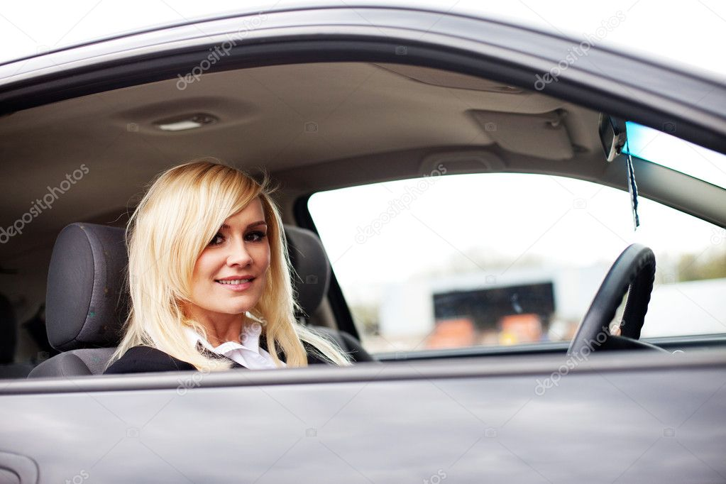 Closeup of a smiling woman driver seated at the wheel of a car looking back out of the window at the camera — Stock Photo #10343094