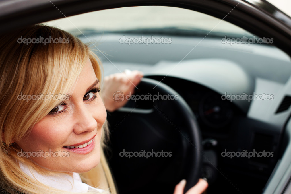 Closeup of a smiling woman driver seated at the wheel of a car looking back out of the window at the camera — Stock Photo #10343195