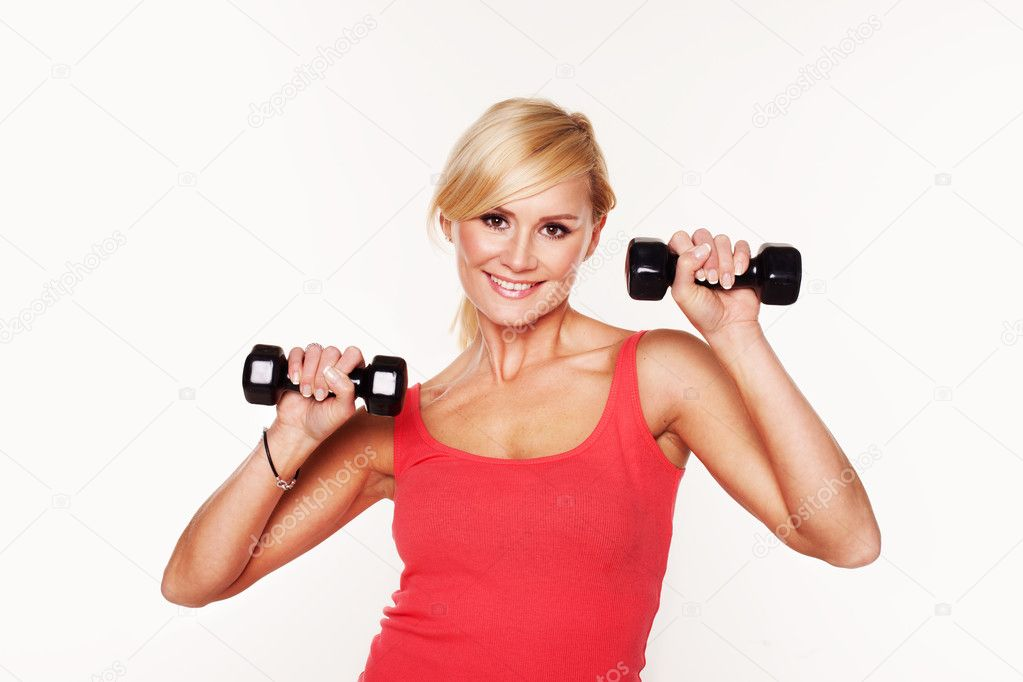 Fit smiling blonde woman in shorts lifting a pair of dumbbells to shoulder height as she exercises and works out, isolated on white — Stock Photo #10356987