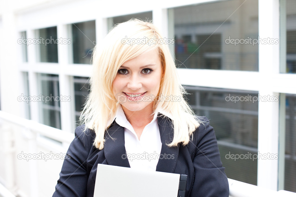 Smiling business woman posing in front of white framed windows — Stock Photo #10411699