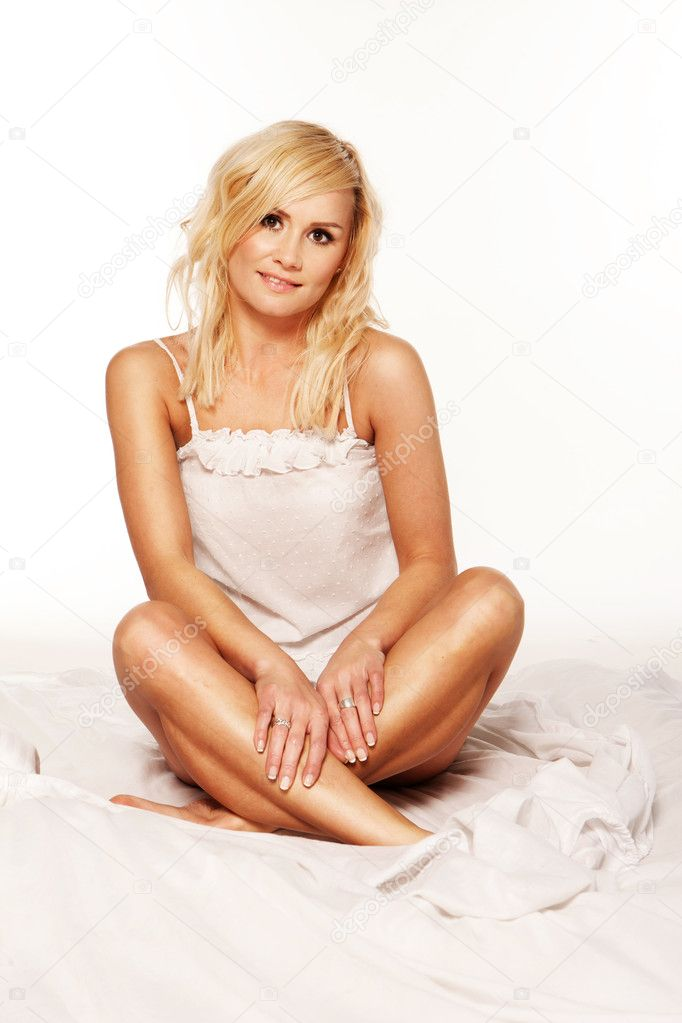 Beautiful blonde girl sitting crosslegged on a bed against a white background  Stock Photo #10461544