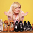 Pretty blonde undecided on which shoes to wear - Stock Photo