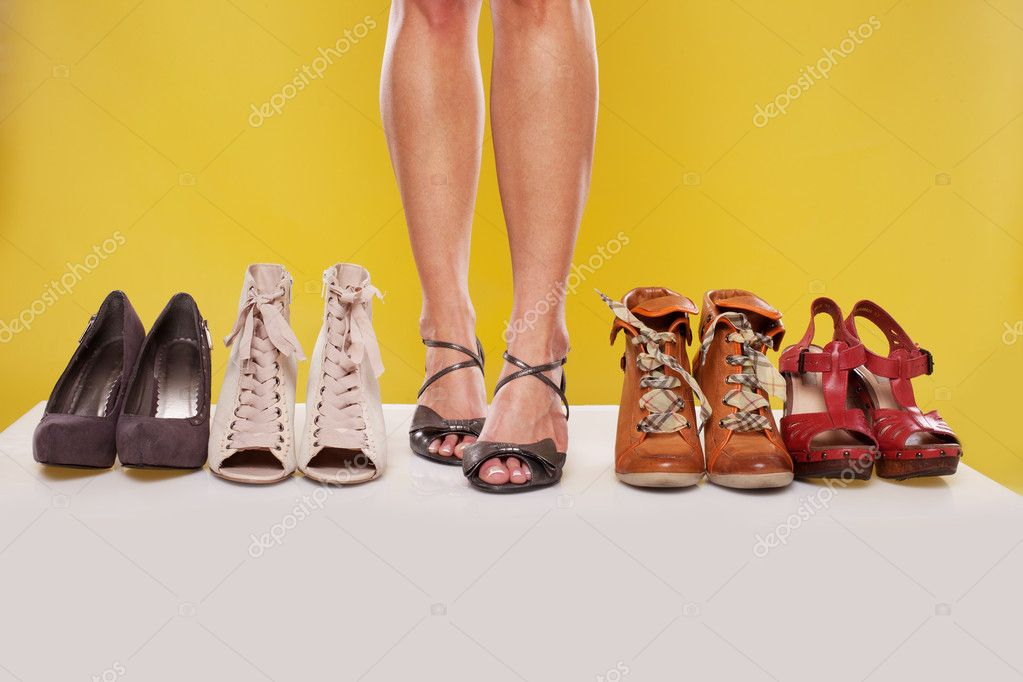 Shapely sexy female legs wearing sandals in the centre of a shoe display on a yellow studio background  Foto Stock #10478085