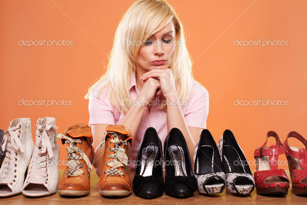 Fashion conscious woman looking at a row of different shoes trying to choose accessories for her outfit — Stock Photo #10478220