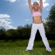 Shapely womexercising on grass — Stock Photo #10628109