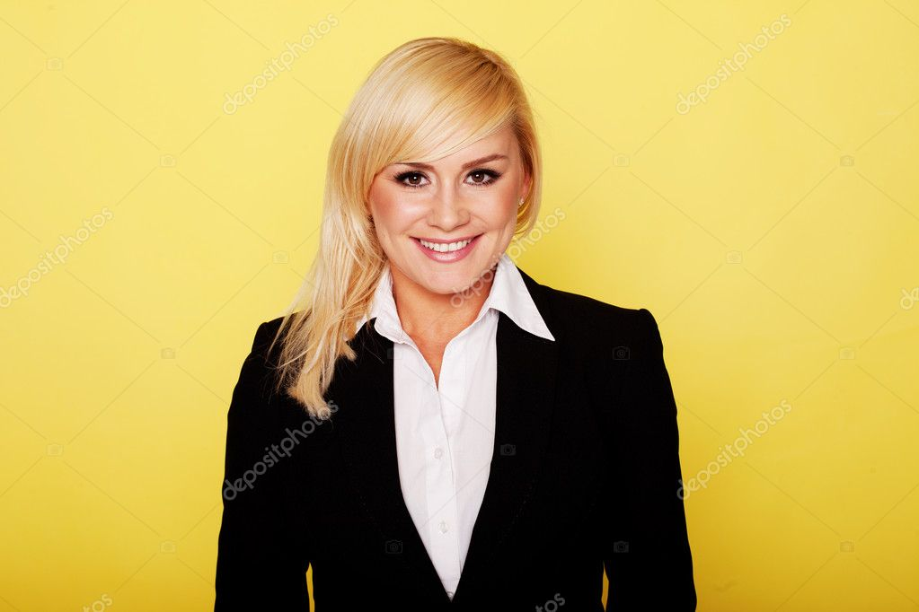 Stylish professional blonde woman in a smart black jacket posing against a yellow studio background — Stock Photo #10628274
